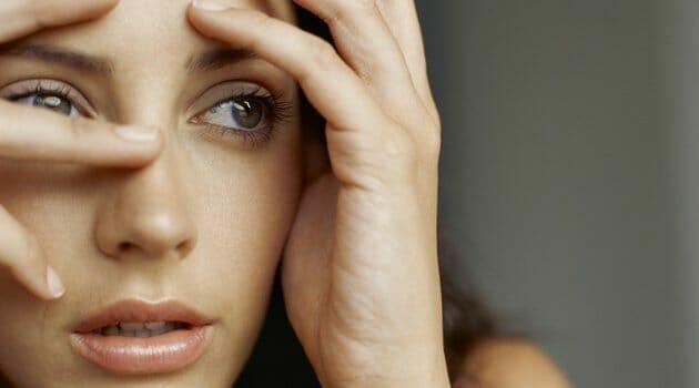 Mulher jovem com a cabeça apoiada em suas mãos, representando ansiedade generalizada