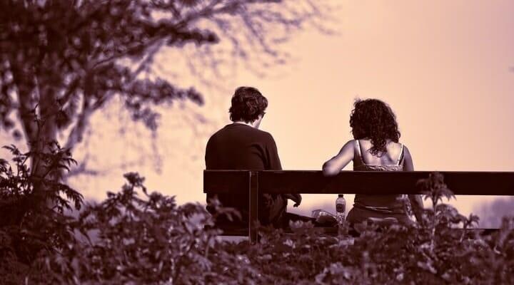 Casal triste sentado em um banco de praça, vistos por trás.