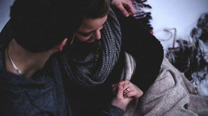 Homem confortando a esposa, segurando sua mão.