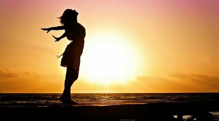 Contorno de uma mulher na praia com o sol ao fundo, mostrando-se feliz