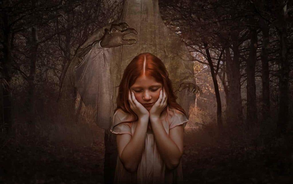 Foto de uma menina com uma floresta escura ao fundo, representando o pesadelo, um dos sintomas do transtorno de estresse pós-traumático